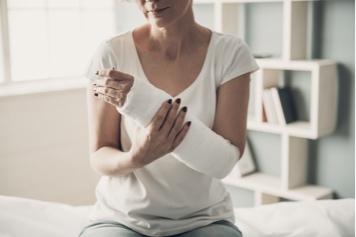 (image) femme tenant son bras dans le platre