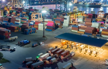 (image) port de nuit avec camions et containers