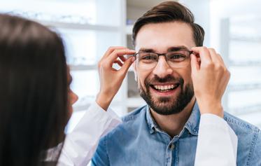 (image) opticienne plaçant sur le visage d'un particulier ses nouvelles lunettes