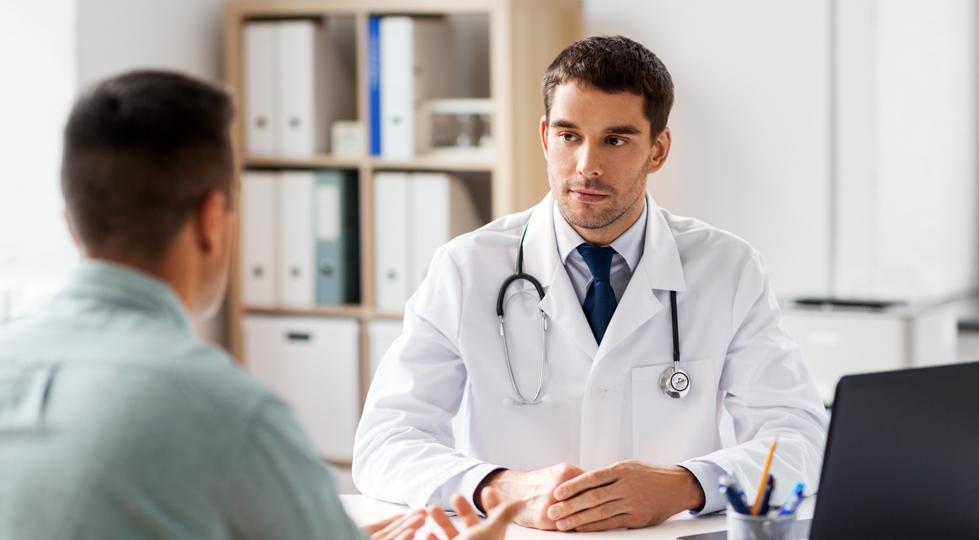 (mage) un médecin et son patient assis devant un bureau face a face