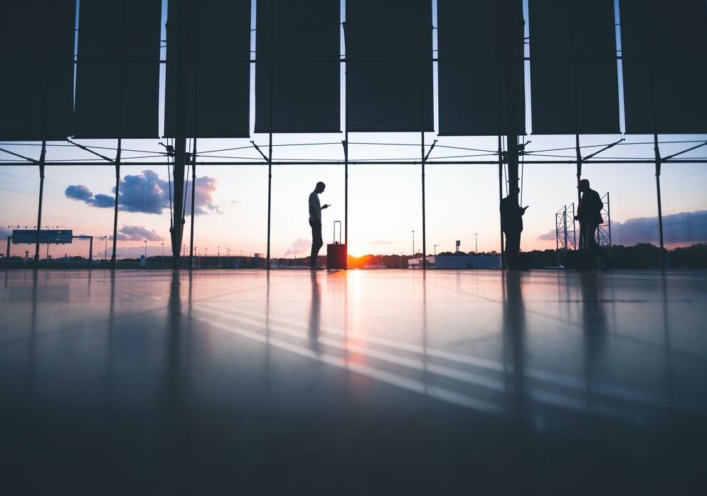 (image) silhouettes à contre jour dans un aéroport avec couché de soleil