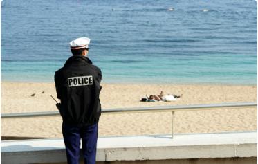 (image) policier de dos regardant la mer