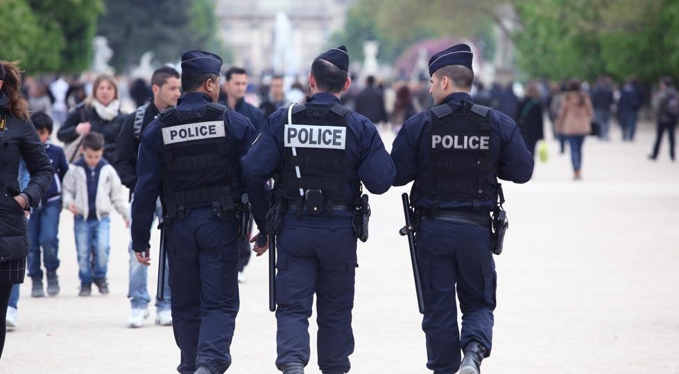(image) trois policiers de dos qui marchent dans la rue