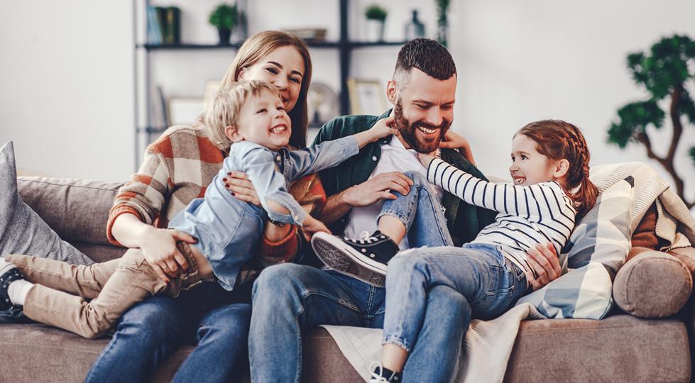 (image) famille qui joue sur le canapé