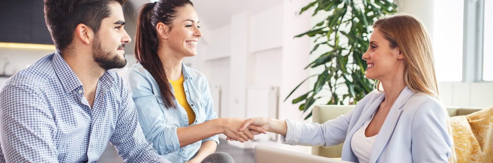 (image) couple serrant la main à une agent immobilier
